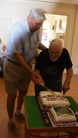 Two founder members Norman and Bert cutting the anniversary cake