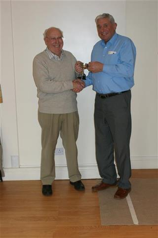 Bert presents Pat with the trophy for winning the skittles with a max score of 9