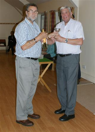 Bert presents Lionel with the trophy for winning the skittles
