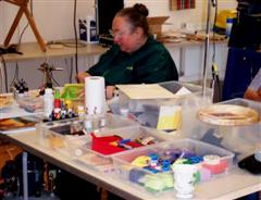 Jennie at her worktable and surrounded by colour